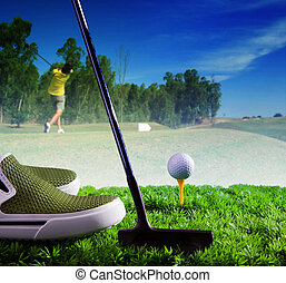 golf ball and putter on green grass of course against young man