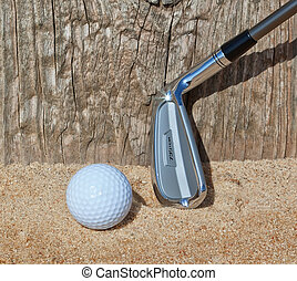 Golf ball and stick inverted wooden support in the sand. Close-up.