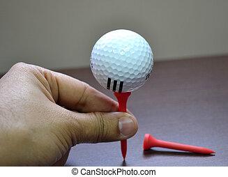 Golf ball balanced on tee in hand