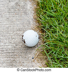 Golf ball - Close up dirty golf ball on the cart path