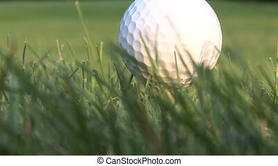 Golf ball - Close up of a golf ball in the grass, zoom out