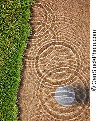 Golf ball drop in water bunker near green grass