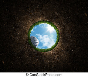 Golf ball falling over the edge into the hole
