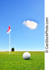 Golf ball in front of flag - Golf ball in front of a flag on...