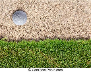 Golf ball in sand bunker near fresh green grass