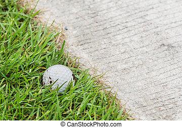 Close up dirty golf ball on grass near the cart path