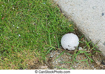 Golf ball near the cart path - Close up dirty golf ball on...