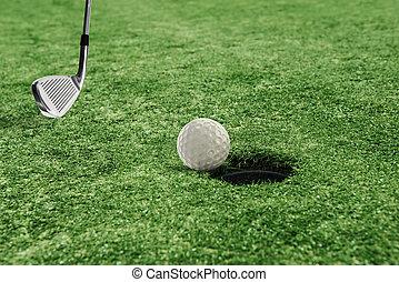 Golf ball near the hole in a grass field