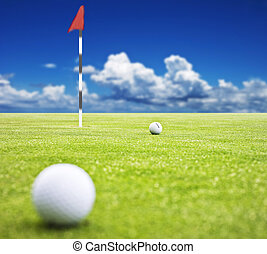 Golf ball on a putting green with the flag in the background...