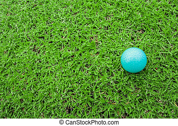 golf ball on a tee in green grass course