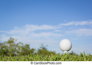 Golf ball on a tee with sky background