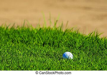 golf ball on grass near bunker
