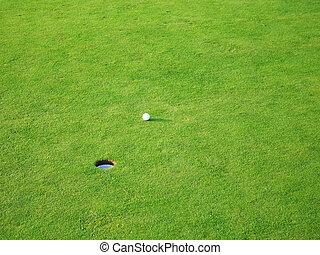 golf ball on grass near hole