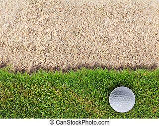 Golf ball on green grass near sand bunker