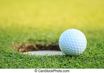 Golf ball on lip of cup in course - Close up golf ball on...