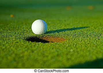 Golf ball on next to hole 5 - White golf ball on putting...
