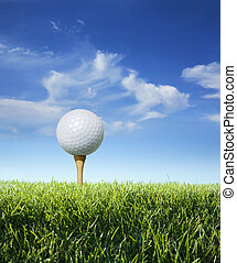Golf ball on tee in grass viewed close up - Low angle, close...