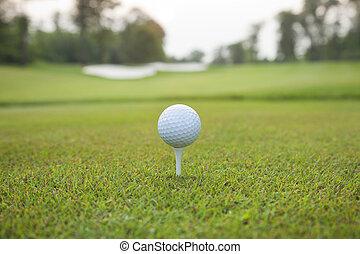 Golf ball on tee with defocused bac