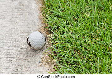 Golf ball on the cart path - Close up dirty golf ball on the...