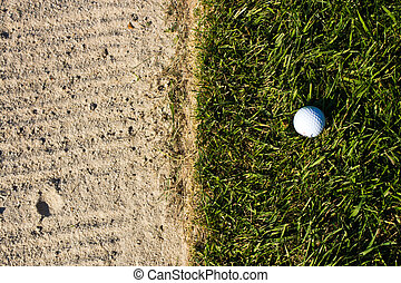 Golf ball on the edge of the sand bunker