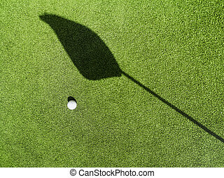 Golf ball on the green, shadow of a flag?on a green,?golf course