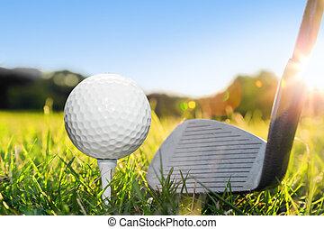 Golf ball on white tee and golf club preparing to shot.