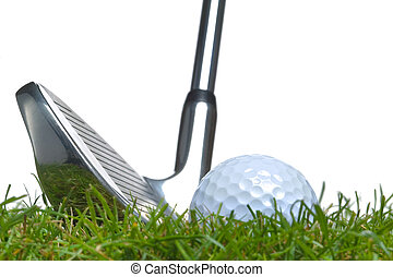 Close up of a golf ball lying in the grass with an iron club lined up for a shot. Studio shot, real grass.