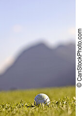 Golf ball with blurred mountains in background