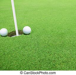 Golf balls near the hole close up