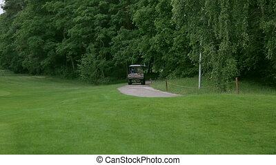 golf car driving away - a golf car is driving down a sand...