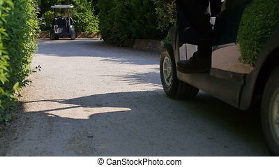 Golf car driving on a sand path