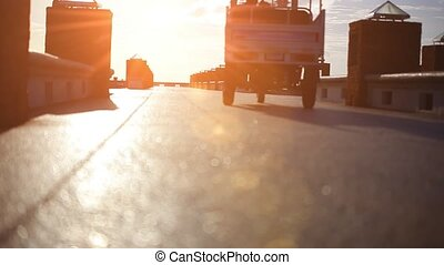 Golf car rides on pier at sunset and man in hat goes to the sun. Video