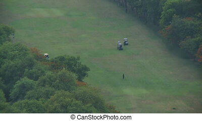 Golf carts driving on a field - A high angle shot of golf...
