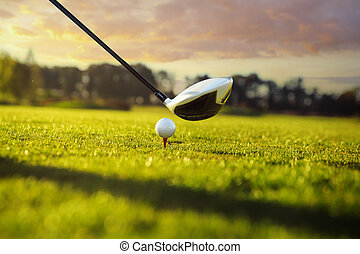 Golf club and ball in grass - Golf ball on tee in front of...