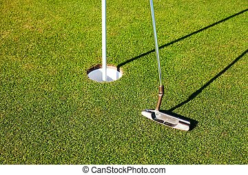Golf club and cup on green, closeup