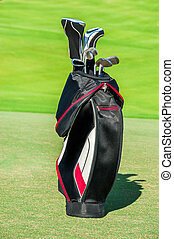 Golf club. Bag with golf clubs Green golf field and ball in...
