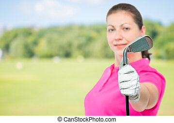 golf club in hand a golfer close up in focus on a background of golf courses