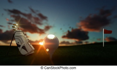 Golf clubs and ball on tee with red flag against beautiful timelapse sunrise, focus shift, zoom out