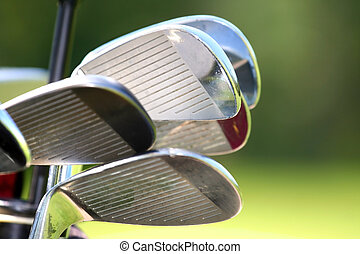 Golf Clubs - Close up shot of shiny golf clubs against green...