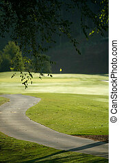A winding cart path leading to golf green.