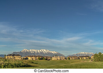 Golf course and homes with a stunning view of snow capped mountain against sky