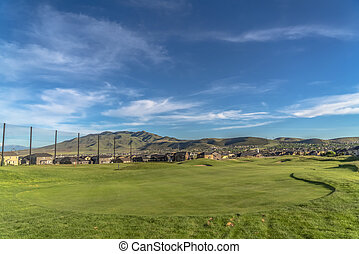 Golf course and houses with view of mountain towering in the distance