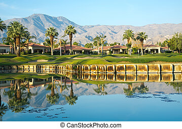 Golf Course at PGA West La Quinta California. This Par 3 hole requires crossing the pond in order to get to the hole. The Palm Trees are reflected in the early morning water.