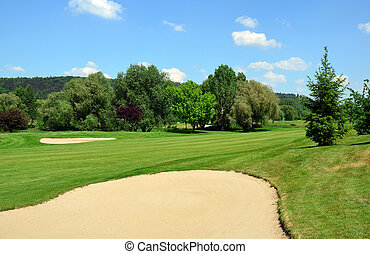 Golf course, green grass, large sand pit, trees