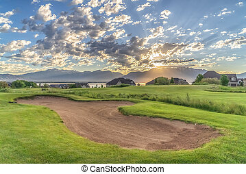 Golf course homes lake and mountain under sun and cloudy blue sky at sunrise