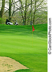 Golf Course In Springtime - a golf cart sits atop a hill...