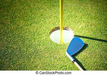 Golf cup with club on green background