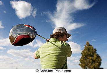 A golfer swinging a large wood (focus on golf club)