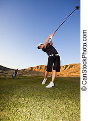 Golf driver swing - A golfer driving the ball down the ...