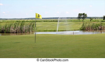 golf field with flag and pond